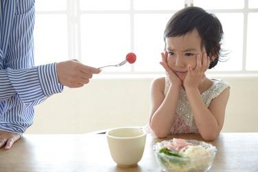 子供に野菜野菜を食べさせる画像